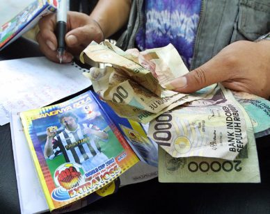An Indonesian hold his betting money during a soccer bet on the World Cup 2002 Germany - Ireland match in Jakarta 05 June 2002. The teams will meet today.  AFP PHOTO/Oka BUDHI