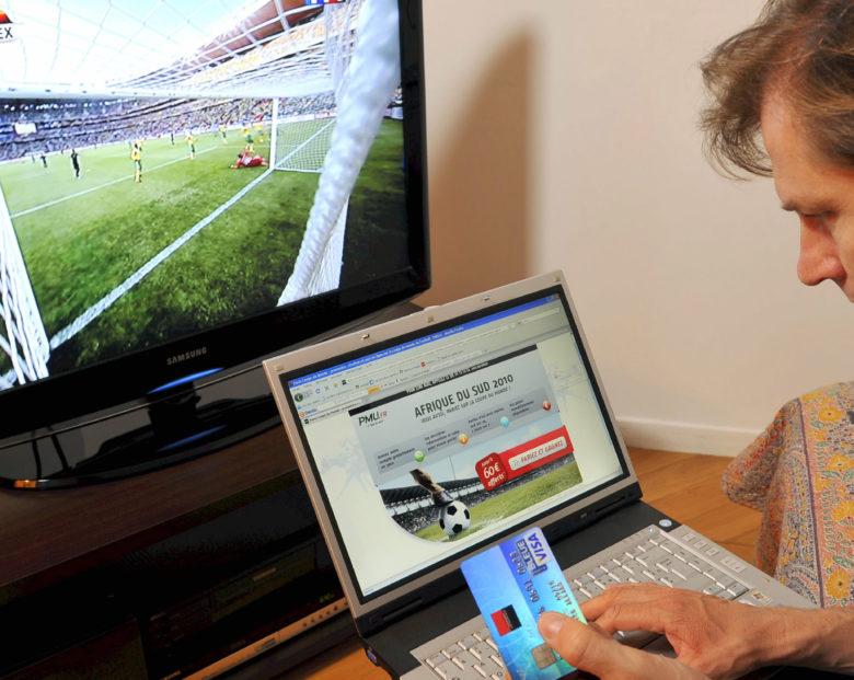 Homme devant sa television pendant un match de la Coupe du monde de football. Carte Bleue Visa, carte de credit, paiement. Paris sportifs sur internet  ordinateur portable, jeu d'argent, sport, loisirs